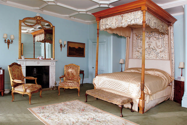 Four Poster Wooden Bed And Two Armchairs In A Light Blue Room