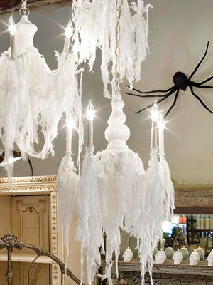 Cobwebs drooped over two white chandelier style light fixtures, all the while a large black spider looms in the background