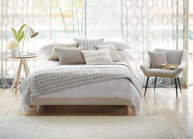 White and cream bedding with grey bed throw, in front of a voile panelled window