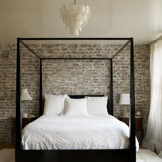 Four poster black bed with white bedding in front of an exposed brick wall
