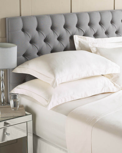 Grey headboard and white mattress and bedding