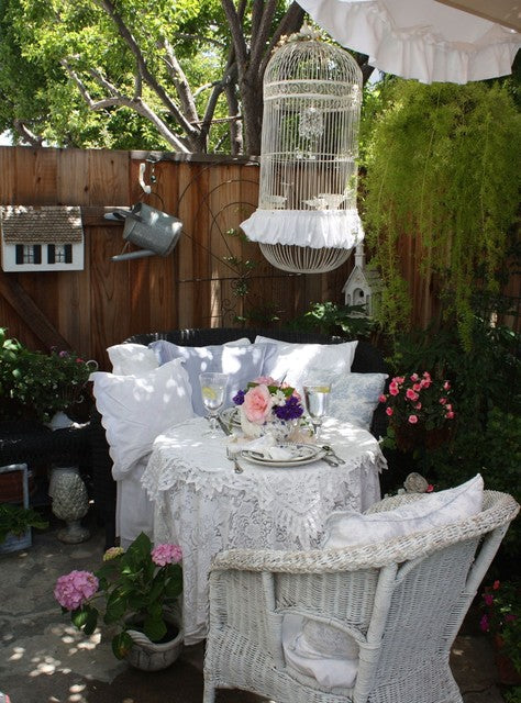 White Wicker Chairs In A Small Garden, With White Birdcage Suspended Above