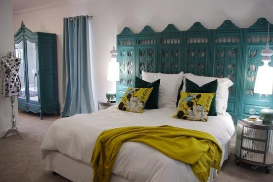 A white double bed in a white bedroom, with teal wardrobe and teal feature headboard behind the bed