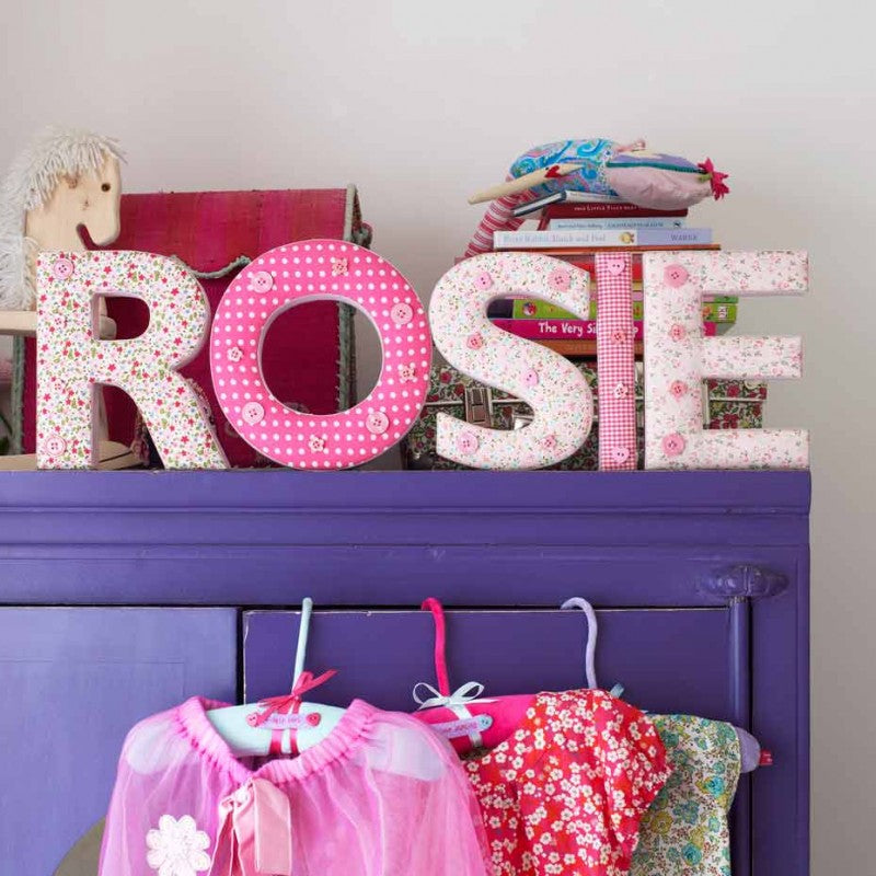 Pink cushions spelling out the name Rosie