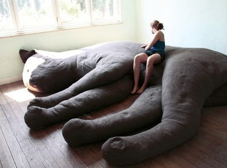 A giant 30 foot to scale bean bag cat, in a large room with a woman sitting on top of it
