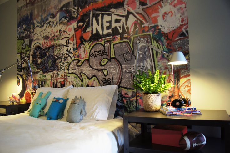 White double bed with graffiti wall art above the bed