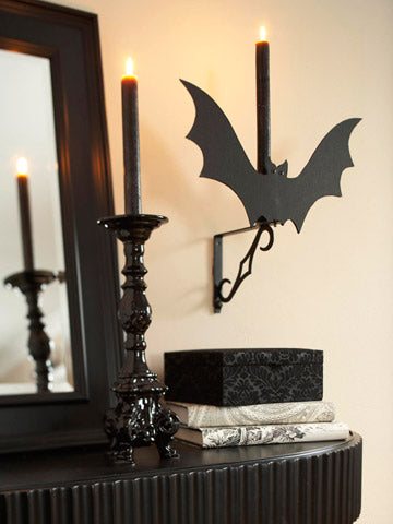 A cutout black bat, and two black candles on a mantel piece