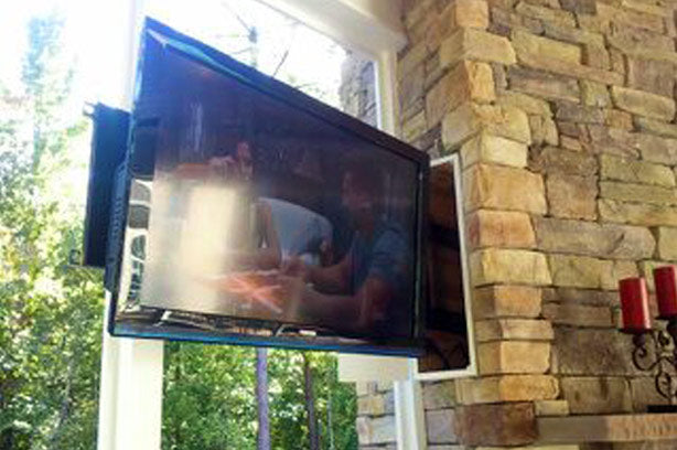 A TV that is mounted to an exposed brick wall, via a rotating arm
