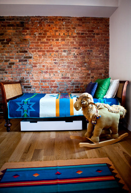 Exposed Brickwork In A Childs Bedroom, With Blue Bedding And Rocking Horse Toy