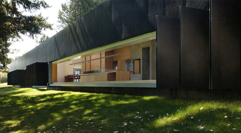 Large black building with lots of black doors that open to allow the outdoor into the home