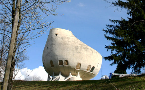 A stone or concrete bowl shaped building at the top of the hill