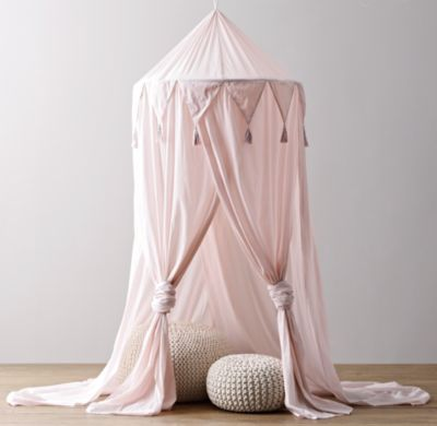 Small pink round canopy covering two woven foot stools