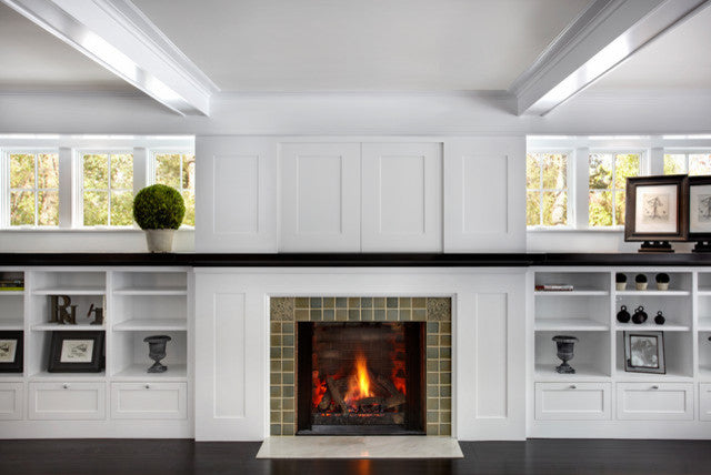 White room, with white storage shelves and tiled fireplace in the middle of the back wall