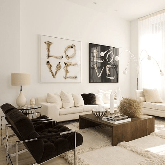 Black and white living room with two white sofas and two black metal armchairs