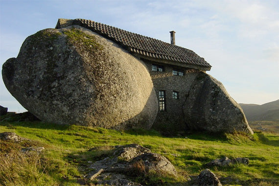 A large stone on the side of a hill that has been carved into a home