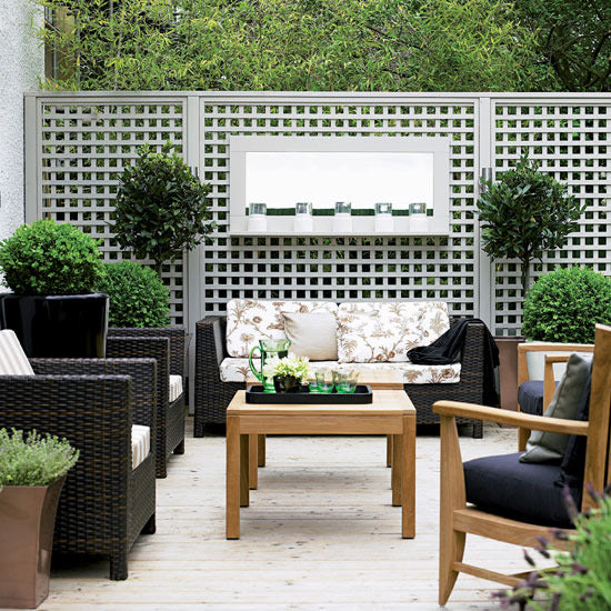 Garden terrace with grey trellis and black wicker furniture