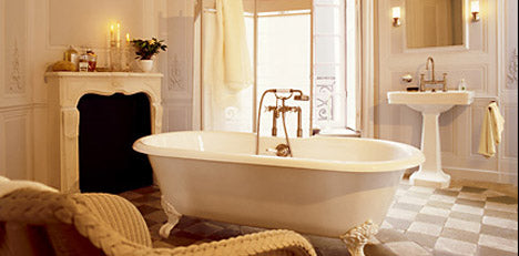 Curved white bathtub with gold fixtures in the middle of a cream bathroom