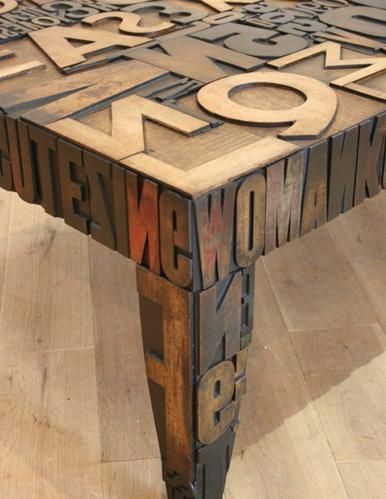 A funky wooden table covered in different sized and colours wooden letters