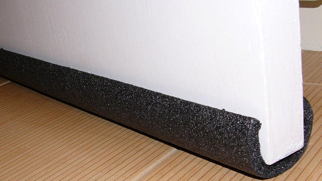 A black foam piper cover fitter to the bottom of a door to provide insulation