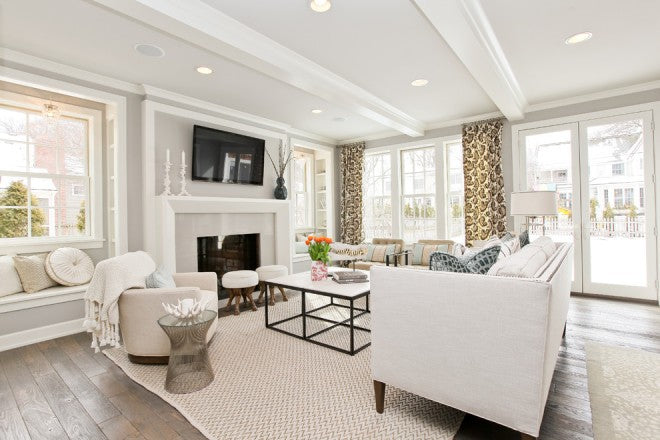 White living room with natural wood floors, white sofa and wall mounted TV above the fire place