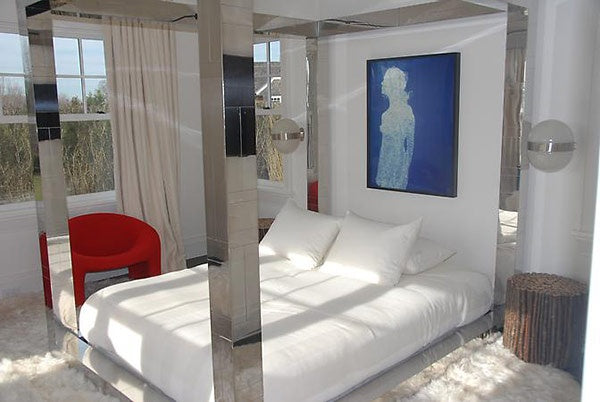 Reflective metal four poster bed in a white bedroom