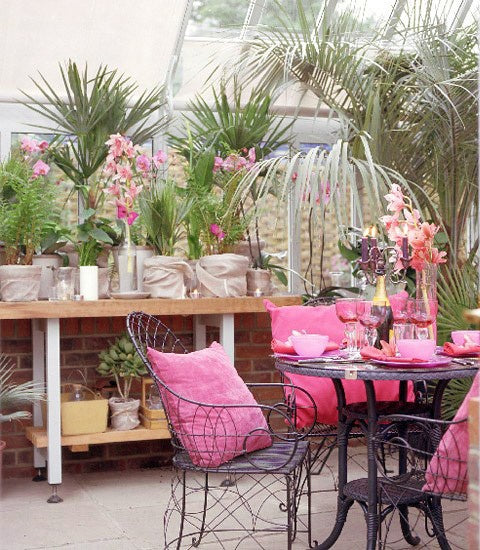 Brick and glass conservatory with small round breakfast table, and pink cushions on the metal seats
