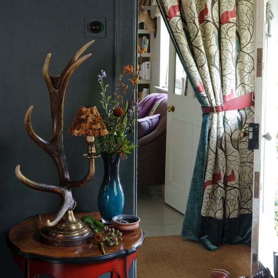 A dark grey hallway with side table containing decorative antler table lamp and blue vase containing flowers