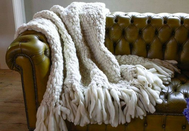 A white wool throw draped over a brown traditional leather sofa