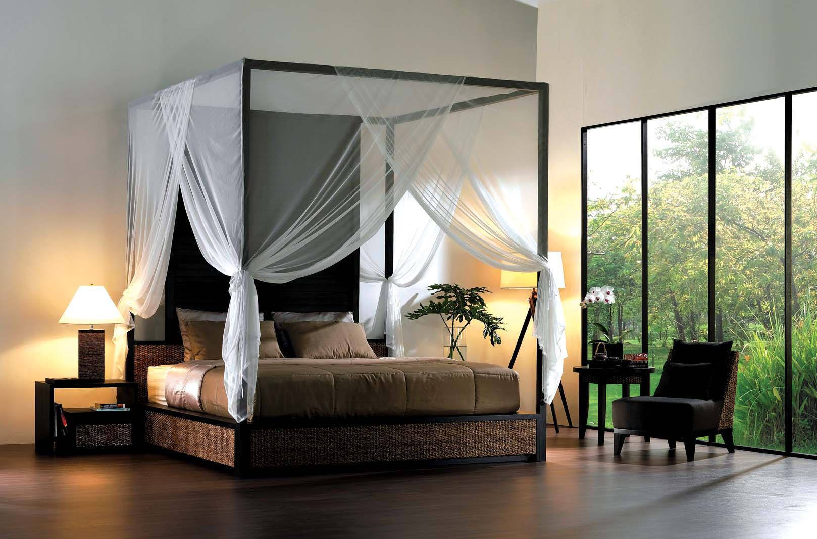 Four poster black bed with beige bedding and white voile canopy over the bed