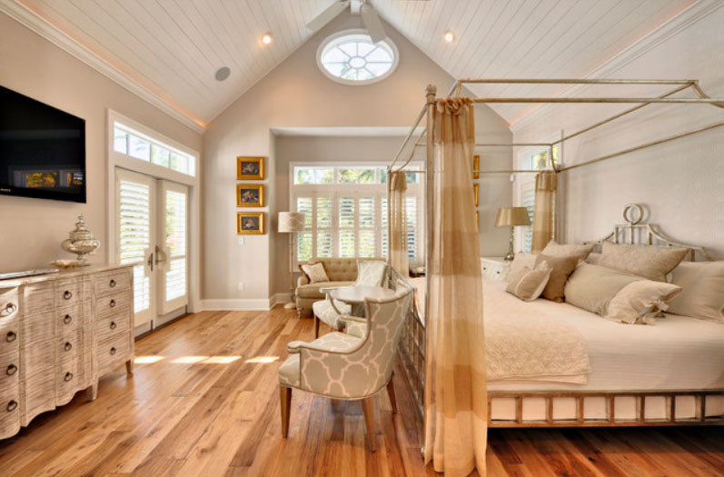 Cream and white sloping roof bedroom with lots of windows