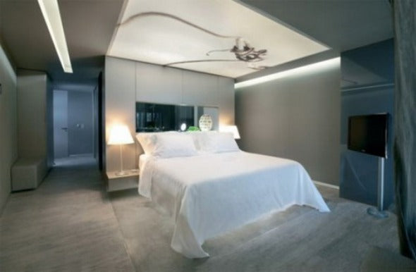 Modern grey and cream bedroom, with white bed and two bedside lamps