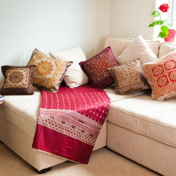 White corner sofa with cream, red, brown and gold cushions