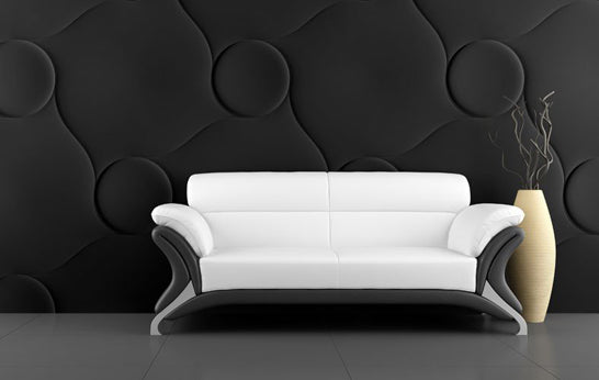 White sofa in front of a black embossed or fabric covered wall