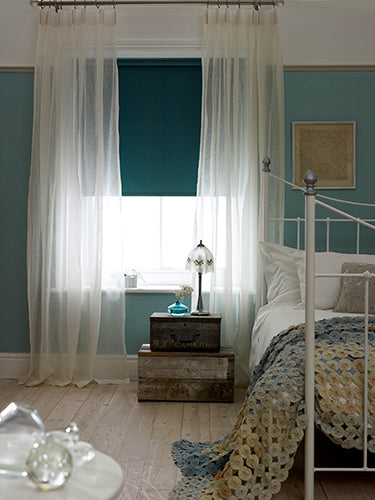Teal and duck egg blue bedroom with white voiles at the window and white metal bed frame