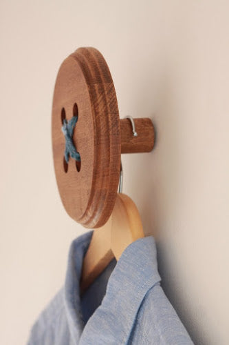 A wooden coat hook that looks like a button