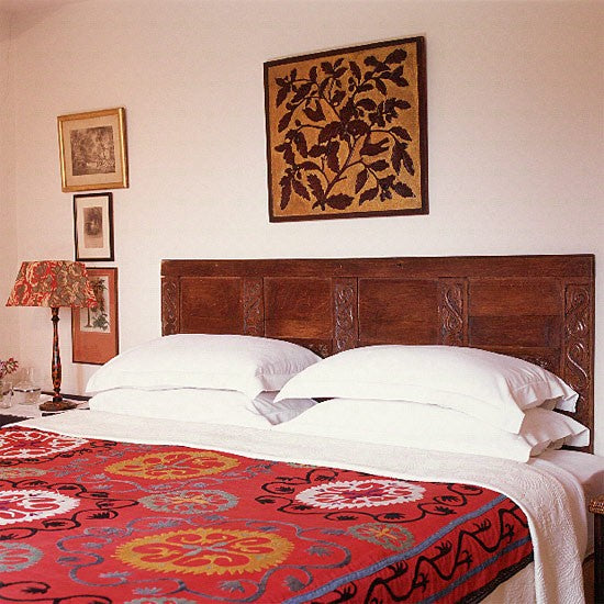 White bedroom with wooden bed and white bedding with red floral throw on top