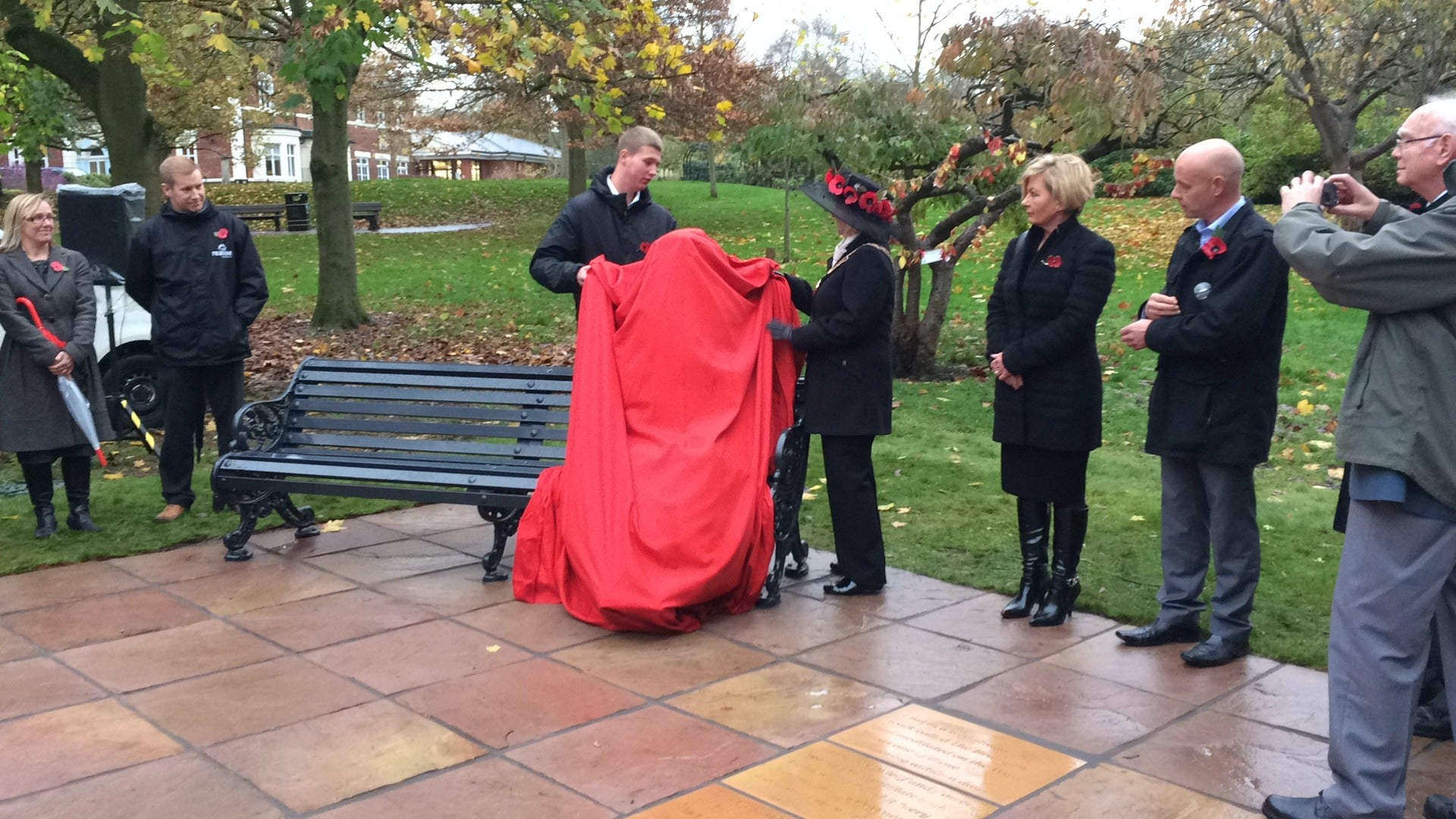 Statue on a bench covered in a red cloth, ready to be unveiled with crowd