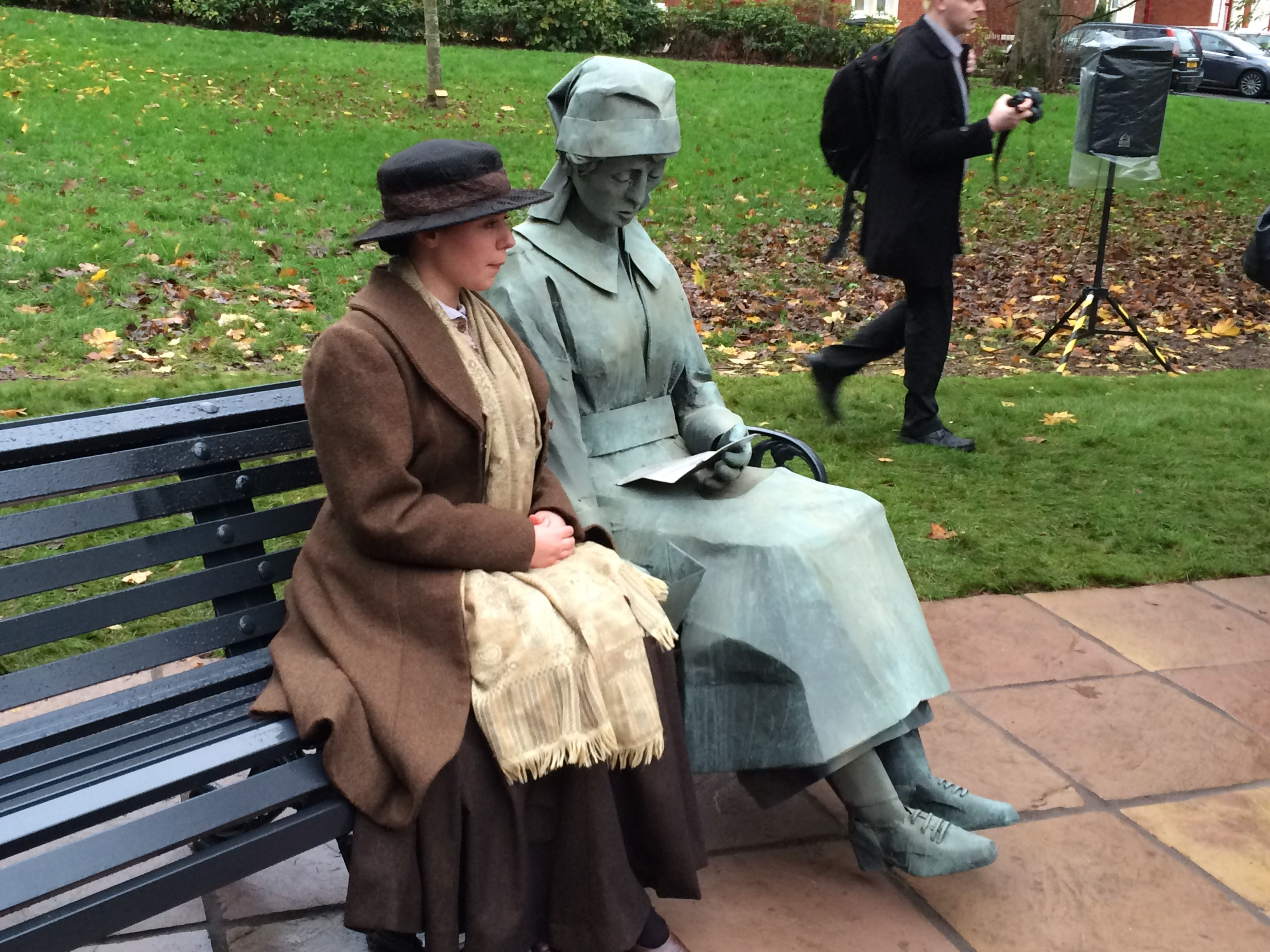 Statue of a woman on a bench, with actress in period cloths sitting next to it