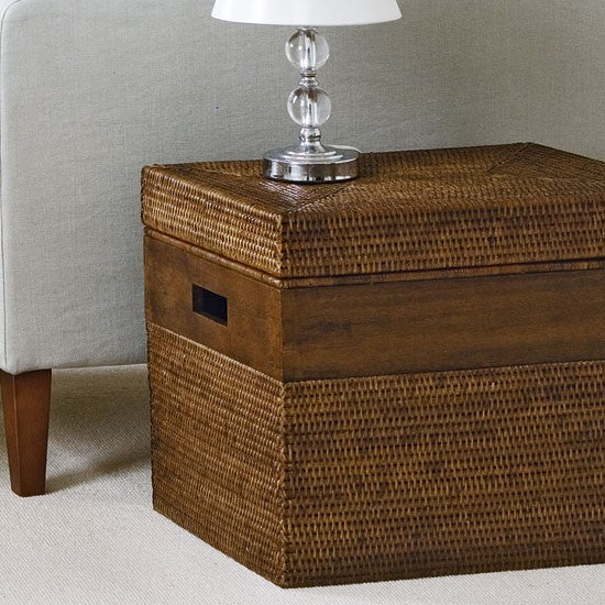 Wicker woven side table, next to a light grey sofa