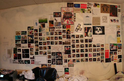 Polaroid photos and posters on a wall in a geometric grid arrangement