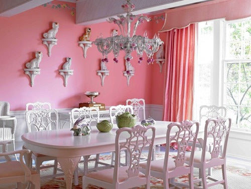 Pink and white dining room with white wooden table and metal chandelier above the table