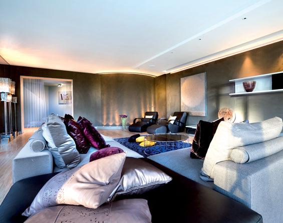 Large living room with dark walls and white ceiling, and grey plush sofas