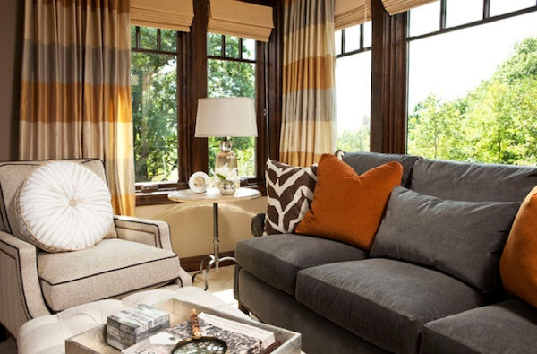 A cream harmonica and grey three seater sofa, with orange cushion and beige and orange striped curtains