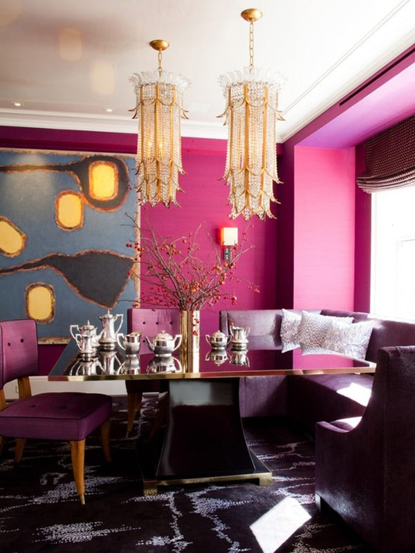 Purple and pink dining room with reflective table, purple seats and two gold and glass chandelier light fixtures