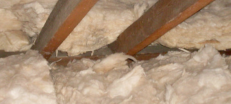 A close up on loft insulation foam and wooded roof beams