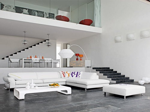 Large living space in white and grey with large white corner sofa and mezzanine floor overhead, with glass wall