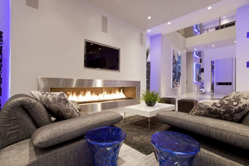 Cream and grey living room with wide fire place, wall mounted TV and purple ambient mood lighting
