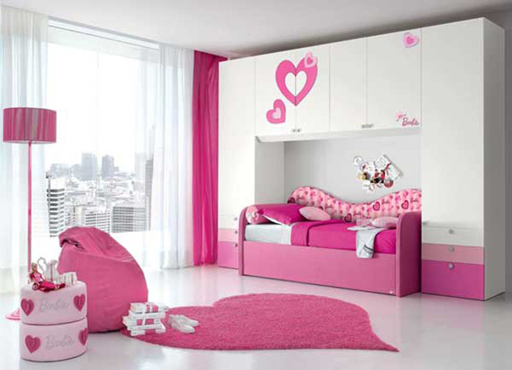 White bedrrom with touches of pink, including a pink lamp, bean bag, bed and rug