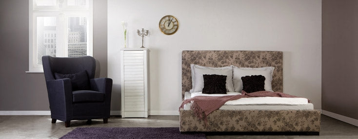 Grey and white spacious bedroom with double bed and black armchair