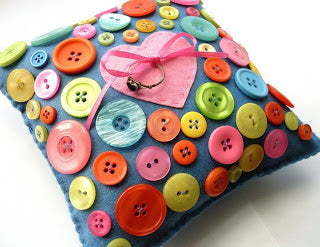 A dark blue cushion covered in pink, blue, yellow, green and orange buttons